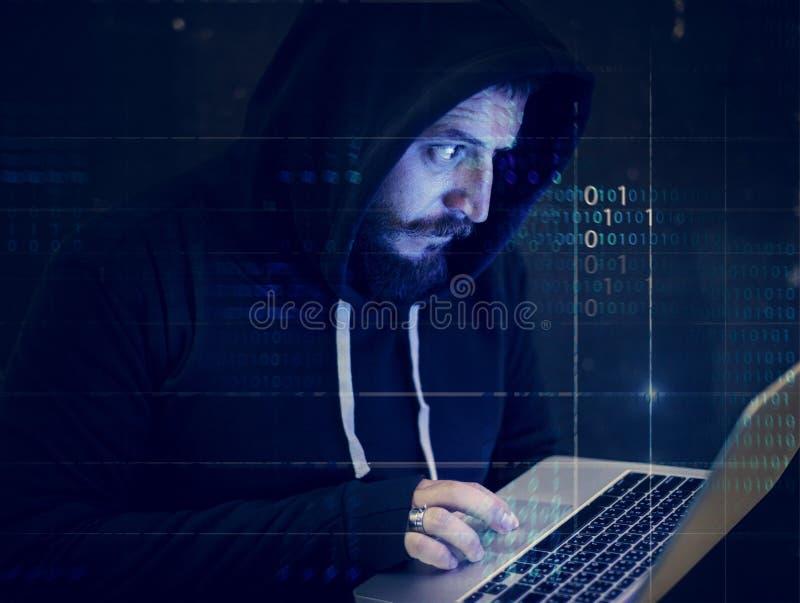 En hacker som försöker att hacka bärbara datorn arkivbild