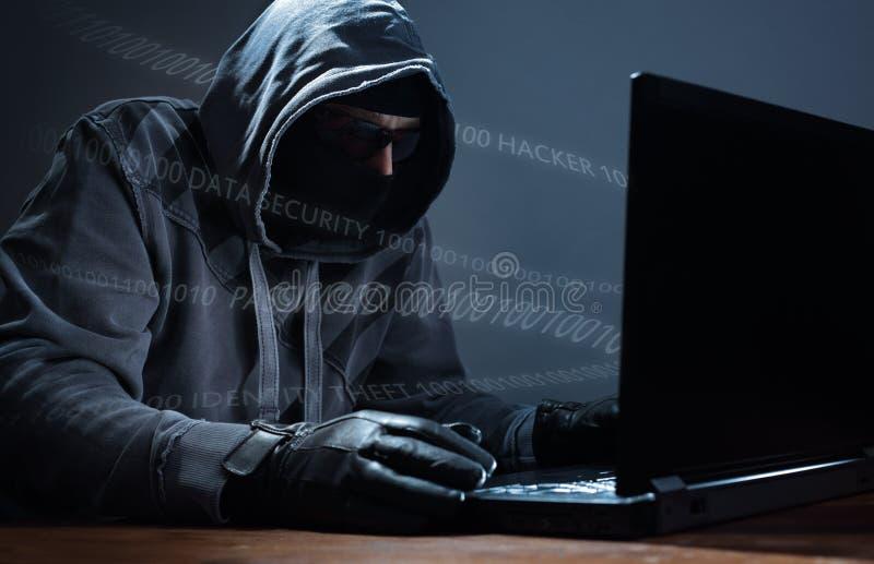 En hacker som stjäler data från en bärbar dator arkivfoton