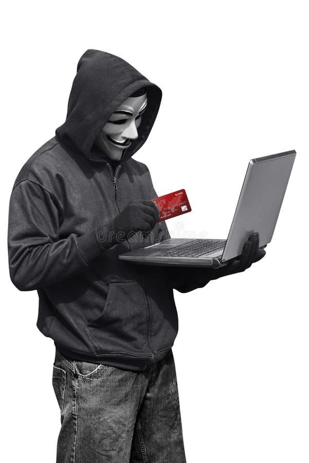 En hackerman som bär bärbara datorn och kreditkorten för anonym maskering den hållande arkivbilder