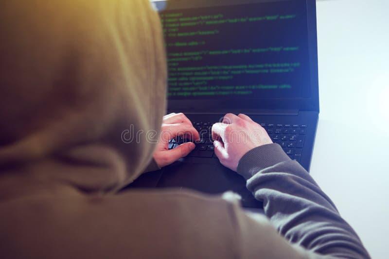 En hackerprogrammerare ser på skärmen och skriver informationen om programkodhackan royaltyfri foto
