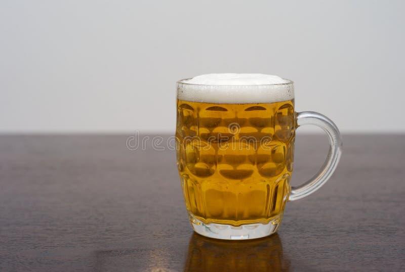 En halv liter av öl på en trätabell royaltyfria bilder