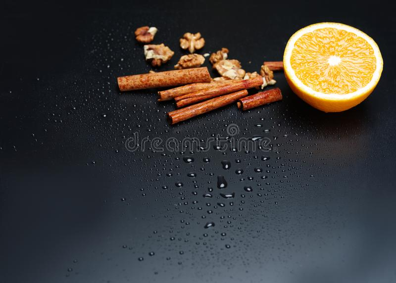 En halva av apelsinen, muttrar och kanel på en mörk bakgrund, närbild royaltyfri bild