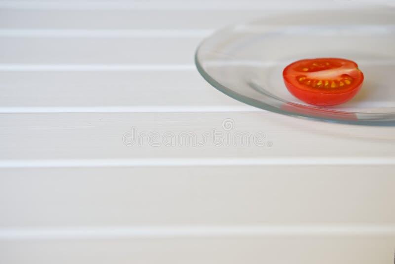 En halva av den nya tomaten ligger på en genomskinlig platta på vita lodisar arkivbild