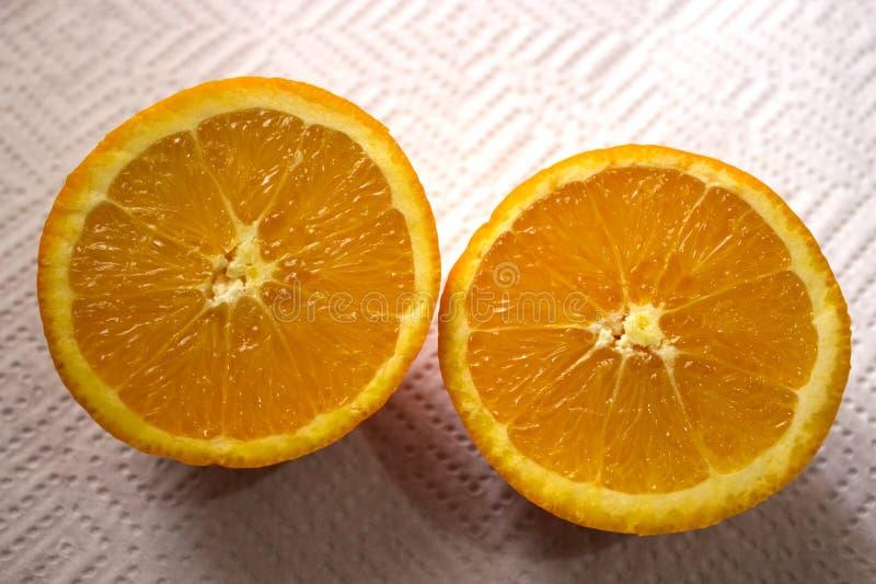 En halverad apelsin på en servett arkivbild