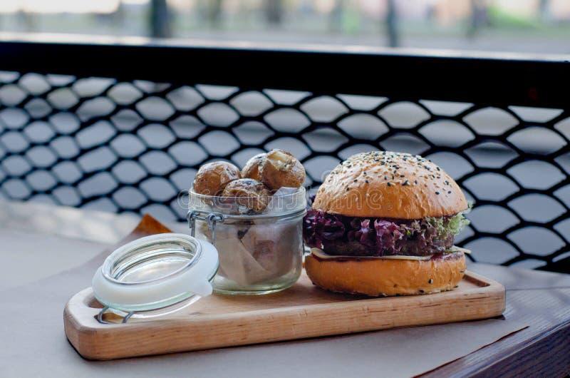En hamburgare med kött och en krus av potatisar står på kafétabellen arkivbild