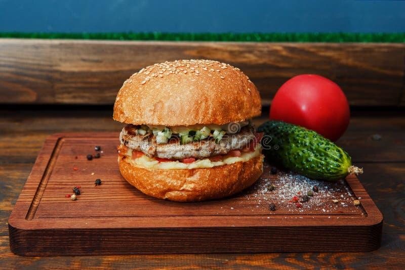 En hamburgare på ett träbräde arkivfoto