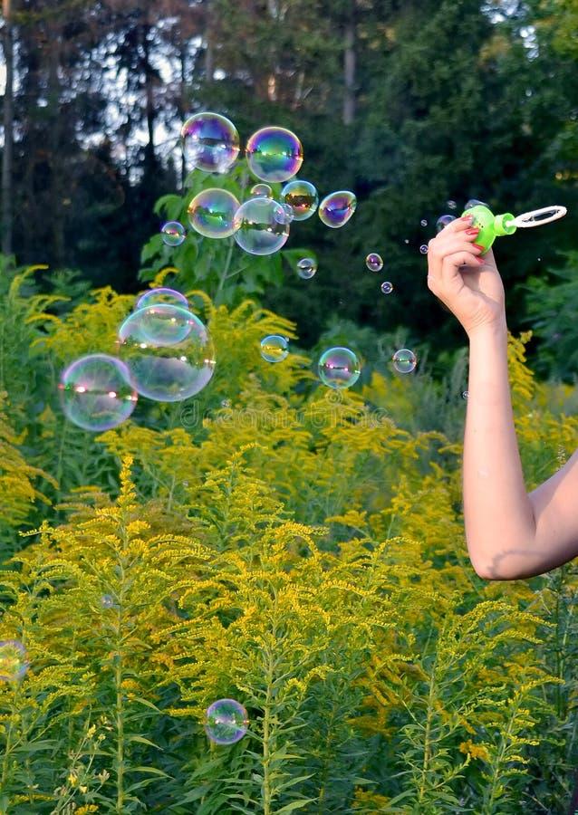 En en hand av flickan soaps beaty bubblor fotografering för bildbyråer