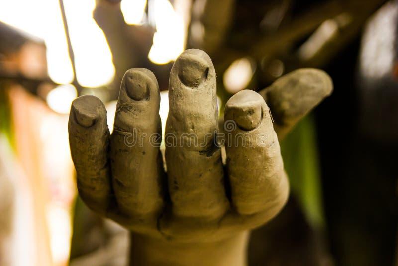 En hand av en staty som göras av lera under konstruktion som frågar för hjälp arkivbilder