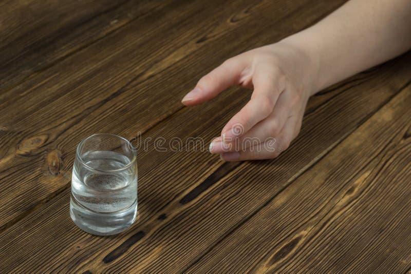 En hand för kvinna` s når för ettexponeringsglas med alkohol, en träbakgrund, en närbild, en hemsk alkoholism arkivfoton