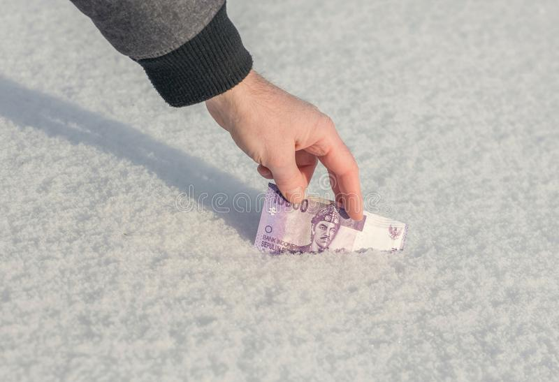 En hand för man` s får tio indonesiska rupiahs för tusentals från snön royaltyfri bild