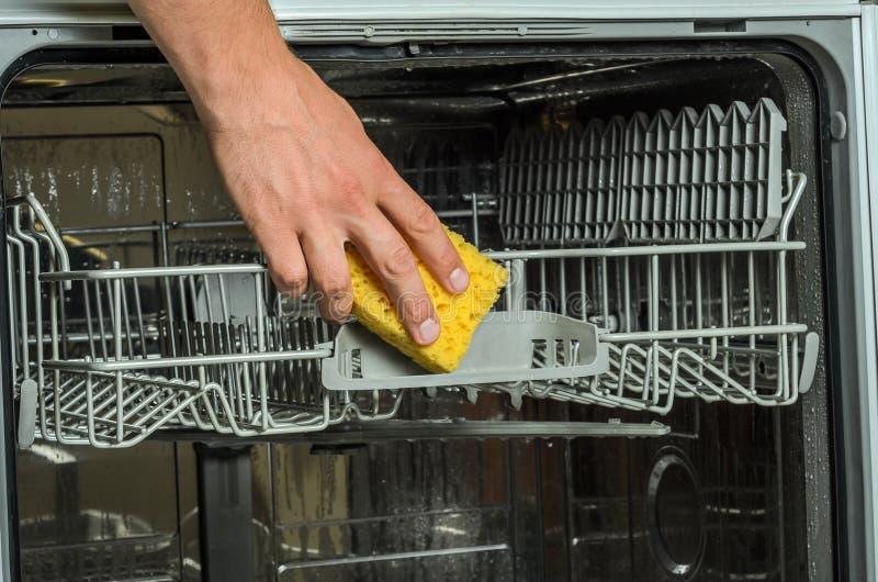 En hand för man` s gör ren en diskaremaskin med en trasa arkivbilder