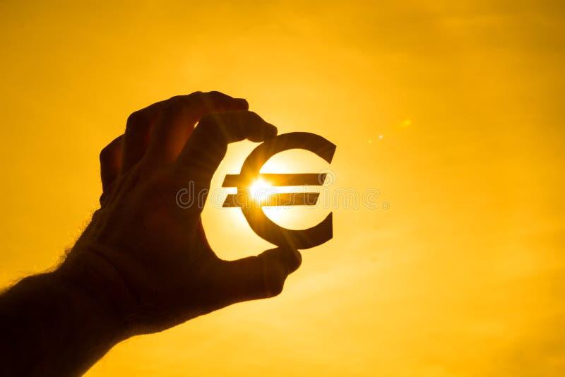 En hand för man` s rymmer eurosymbolet mot ljuset av solen royaltyfria foton