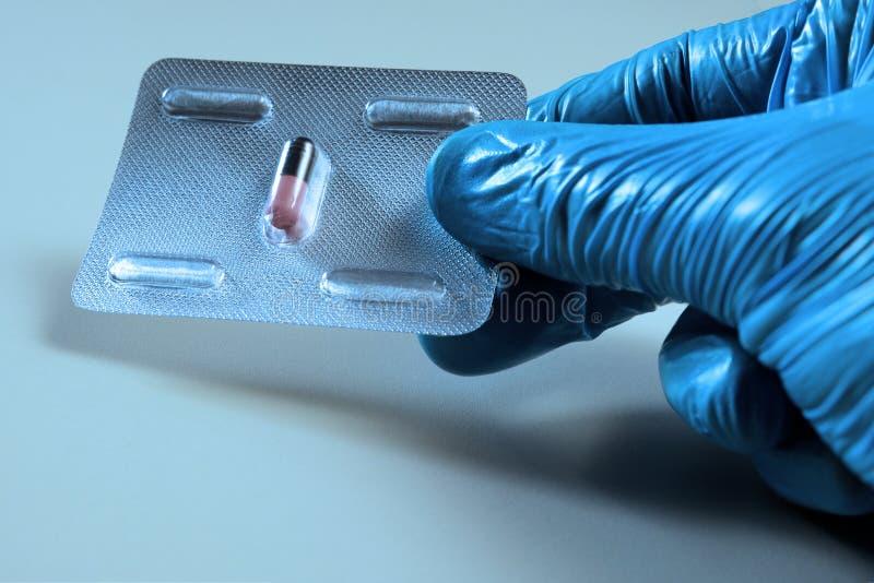 En hand i en blå labbhandske rymmer en blåsa med ett piller Medicinska begrepps-, hälso- och affärs-, sjukdom- och behandlingalte royaltyfri foto