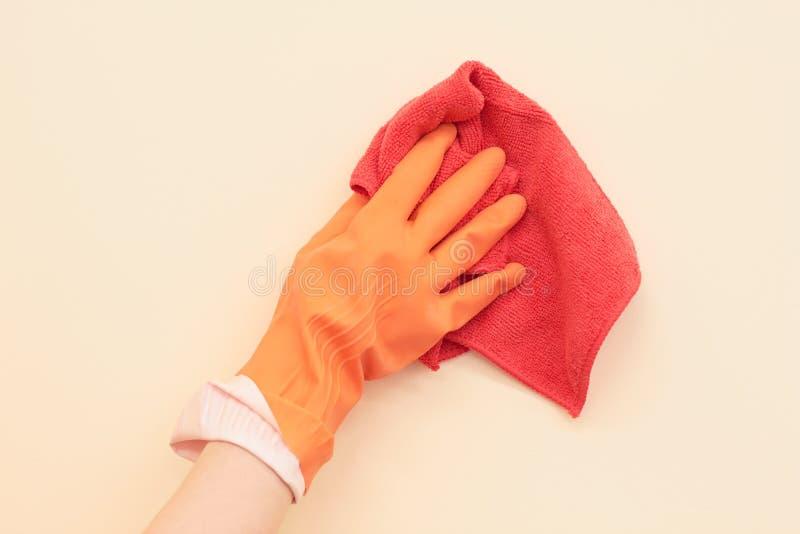 En hand i en handske tvättar väggen arkivfoton
