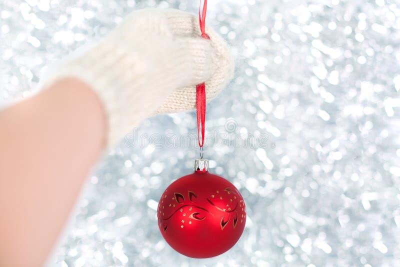 En hand i en vit tumvante rymmer röda nytt års boll på rött band på bakgrund av skinande glitter, vita ljus och mousserar bokeh arkivbild