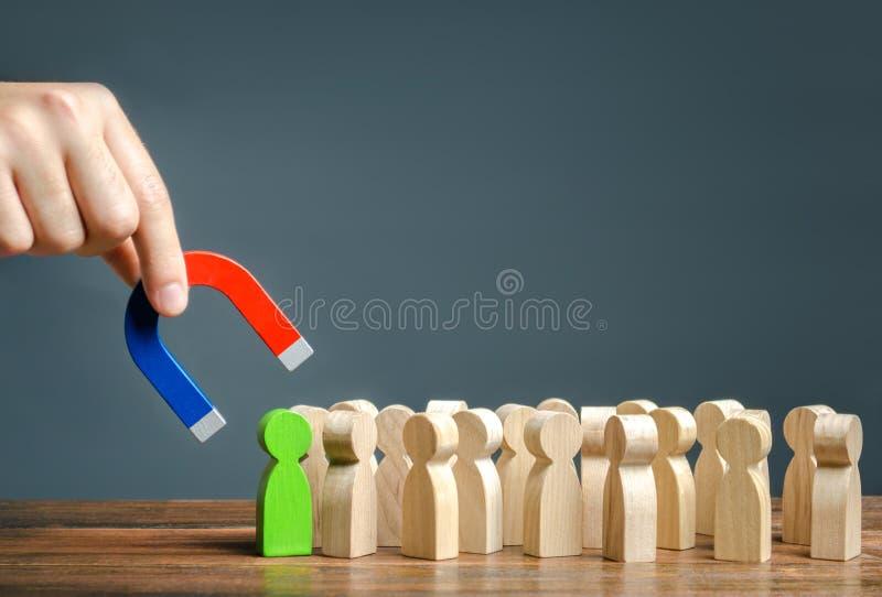 En hand med en magnet försöker att dra ett grönt diagram av en person ut ur en folkmassa Sökande för begåvade arbetare med stor k royaltyfri foto