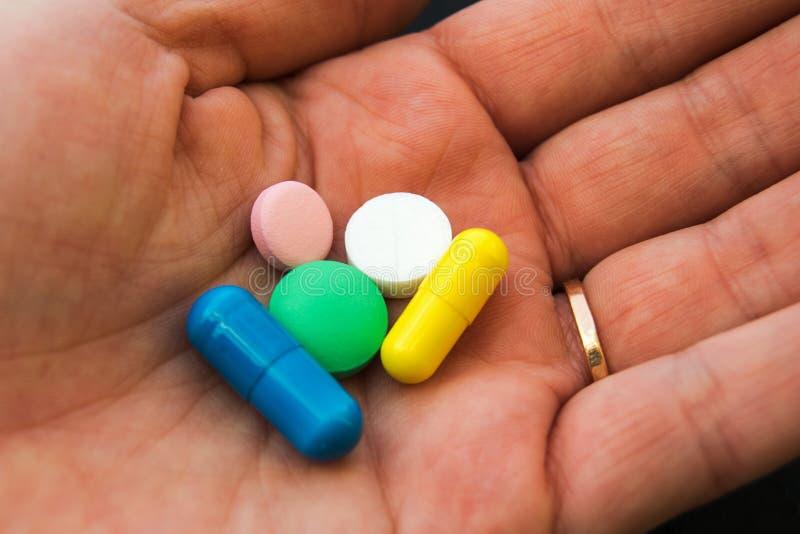 En hand med olika piller royaltyfria bilder