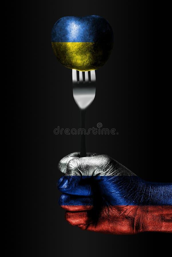 En hand med en utdragen Ryssland flagga rymmer en gaffel, som är på en boll med en utdragen Ukraina flagga, ett tecken av påverka arkivfoton