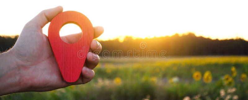 En hand rymmer en röd lägemarkör i solnedgångbakgrunden Begreppet av turism och loppet Navigering och utforskning royaltyfri bild