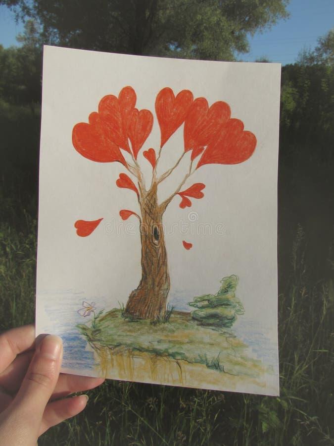En hand rymmer en teckning av ett fantastiskt träd med röda hjärtor i ljuset av stigningssolen vektor illustrationer