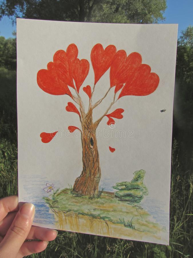 En hand rymmer en teckning av ett fantastiskt träd med röda hjärtor, som ett fel sitter på, i ljuset av stigningssolen royaltyfri bild