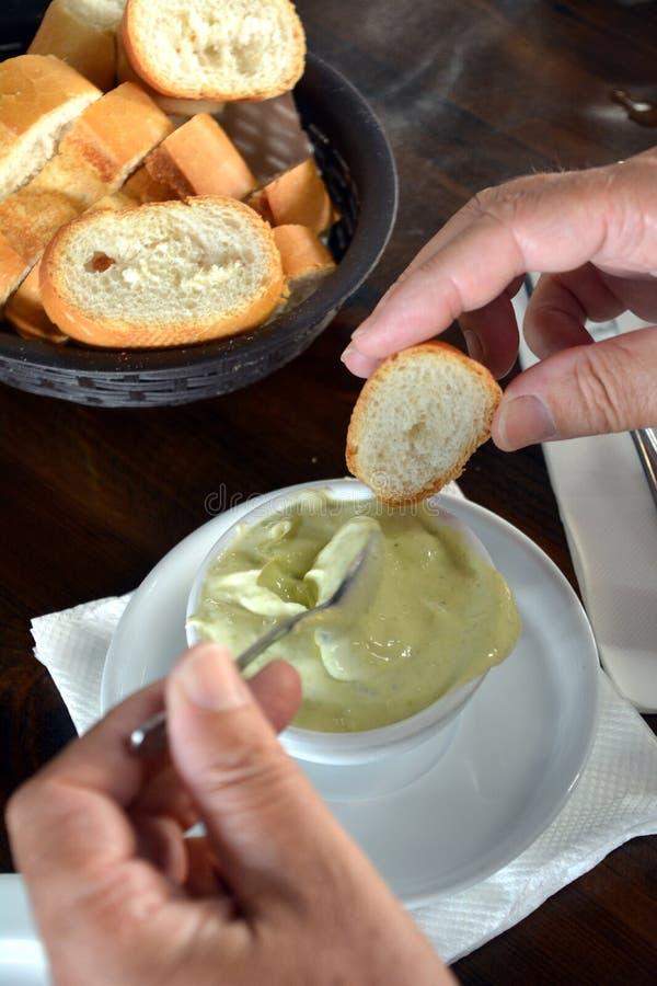 En hand sätter aliolisås på ett nytt bröd Spansk mat arkivbild
