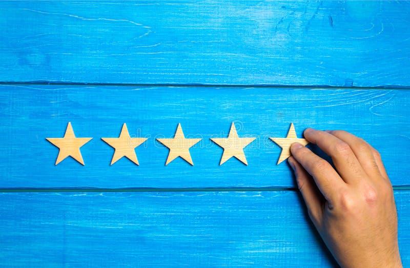 En hand sätter den femte trästjärnan på en blå bakgrund Kritikern ställer in den kvalitets- värderingen Fem stjärnor, den högsta  royaltyfri foto