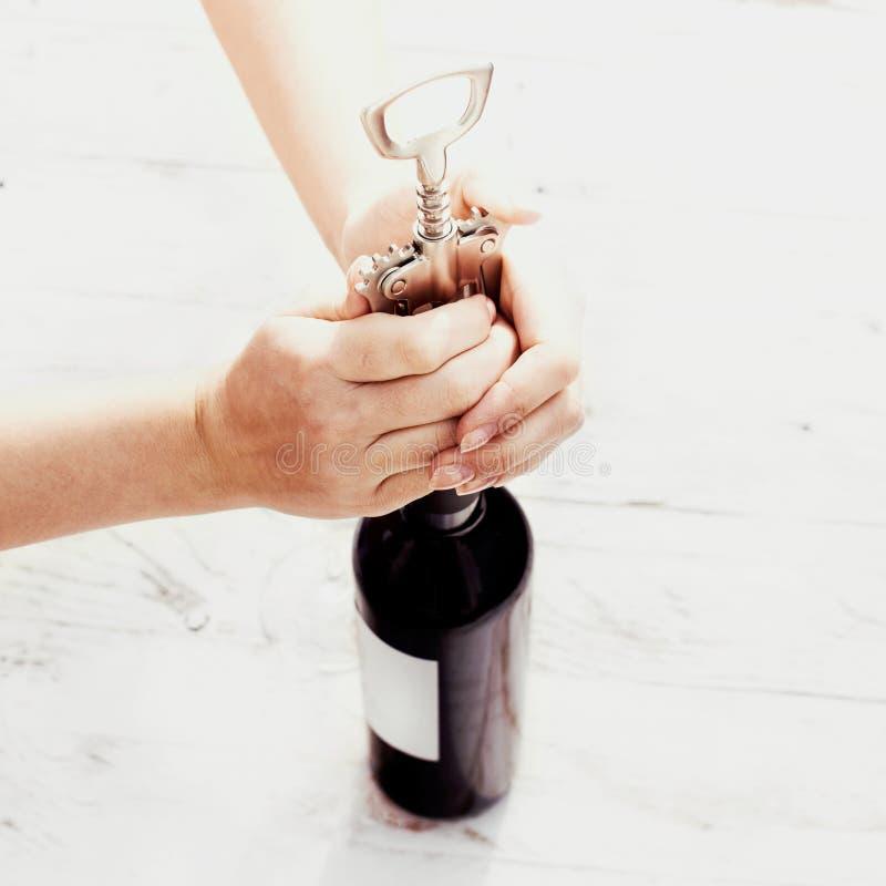 En hand som öppnar en flaska av rött vin med korkskruvet på tappning w royaltyfri fotografi