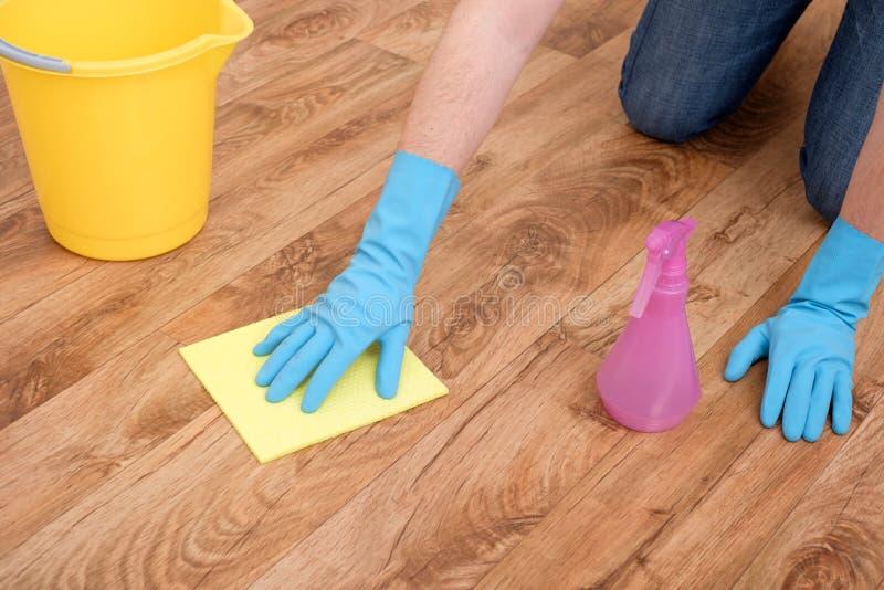 En hand som gör ren en parkett arkivbild