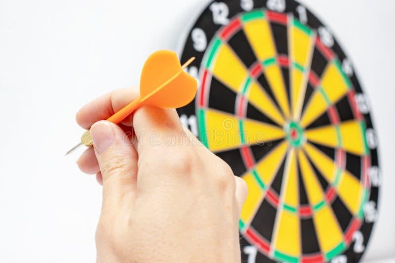 En hand som rymmer en bl? pil klar att kasta den till ett darttavlam?l, strategi och expertis i aff?rsid? royaltyfria foton