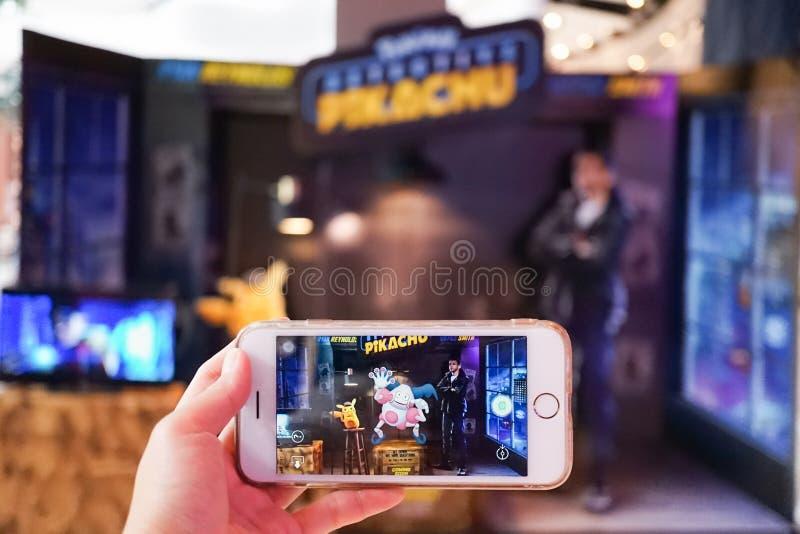 En hand som rymmer den smarta telefonen som spelar Pokemon, går AR-funktionsläget med fokusen på herr far royaltyfri foto
