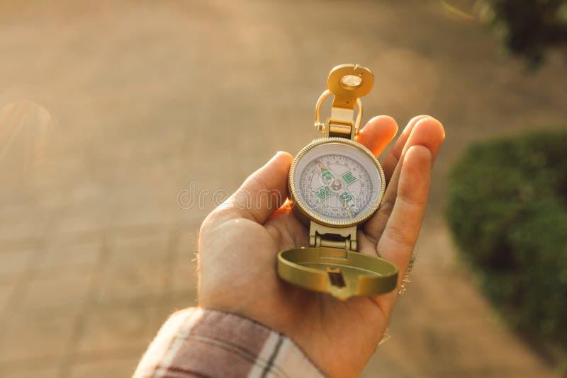 En hand som rymmer en kompass som pekar till norden arkivfoton