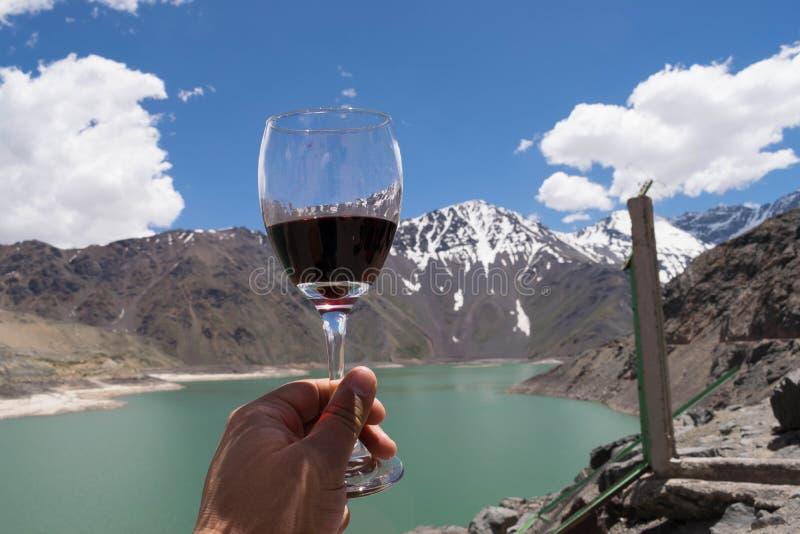 En hand som rymmer ett exponeringsglas av rött vin med den härliga gränsmärket i bakgrunden royaltyfri illustrationer