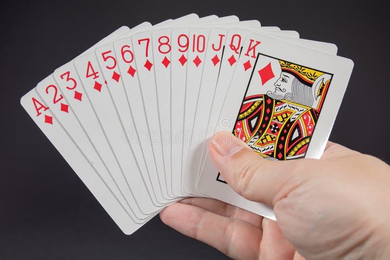 En hand som rymmer följet av diamanter från att spela kort arkivfoto
