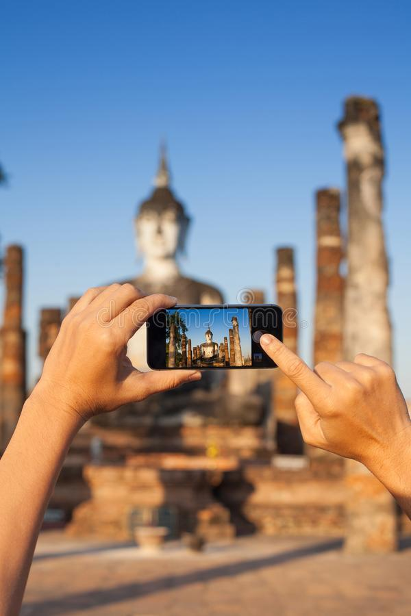En hand som tar fotoet av Buddhastatyn med smartphonen, Sukhothai, Thailand royaltyfri fotografi