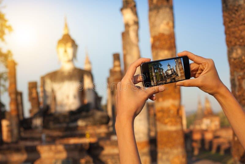En hand som tar fotoet av Buddhastatyn med smartphonen, Sukhothai, Thailand royaltyfri foto