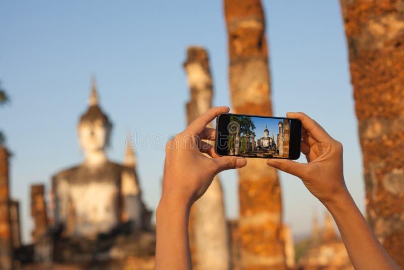 En hand som tar fotoet av Buddhastatyn med smartphonen, Sukhothai, Thailand royaltyfria foton