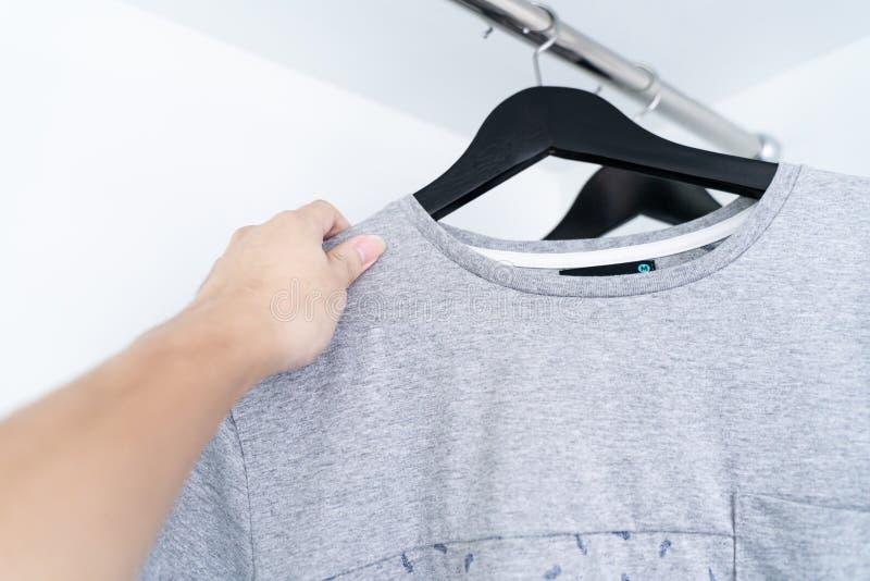 En hand som tar en grå skjorta, gråa skjortor som i rad hänger arkivbilder