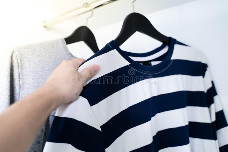 En hand som tar en skjorta, skjortor som i rad hänger royaltyfri fotografi