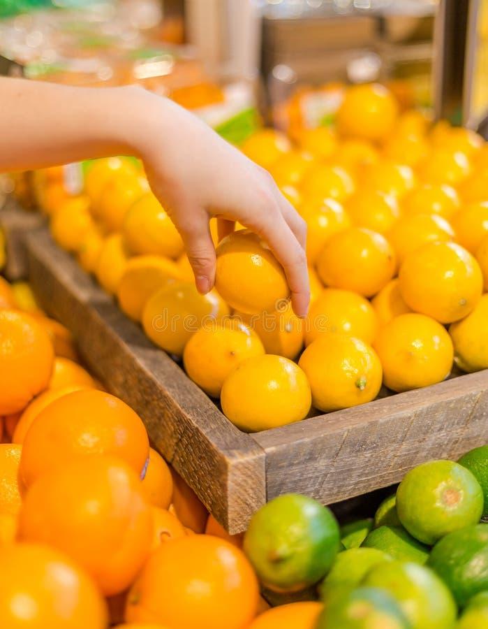 En hand som upp väljer en citron i jordbruksprodukteravsnittet av en livsmedelsbutik fotografering för bildbyråer