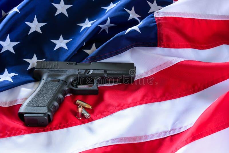 En handeldvapen och kulor på amerikanska flagganbakgrund fotografering för bildbyråer