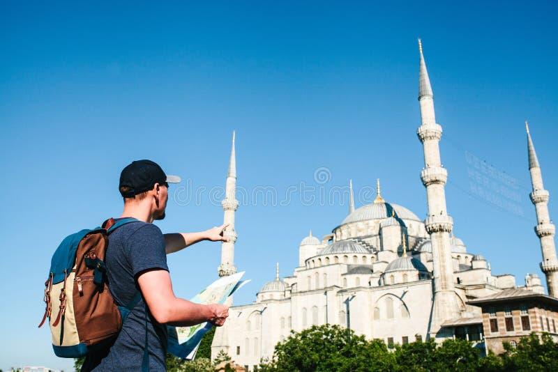 En handelsresande i en baseballmössa med en ryggsäck ser översikten bredvid den blåa moskén - den berömda sikten av royaltyfri foto