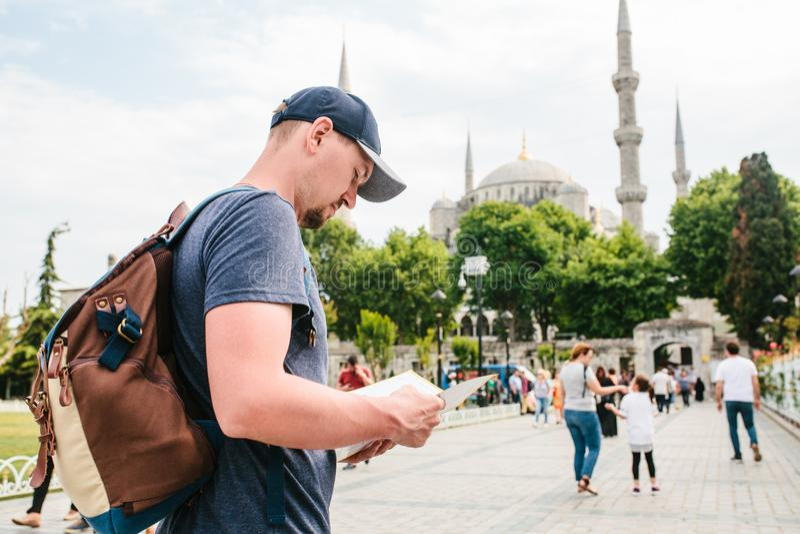 En handelsresande i en baseballmössa med en ryggsäck ser översikten bredvid den blåa moskén - den berömda sikten av royaltyfri fotografi
