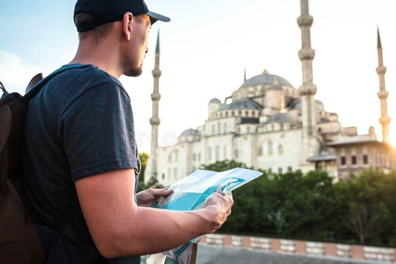 En handelsresande i en baseballmössa med en ryggsäck ser översikten bredvid den blåa moskén - den berömda sikten av royaltyfria foton