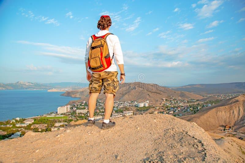 En handelsresande med en ryggsäck på hans baksida står på överkanten av ett berg som beundrar landskapet arkivfoton
