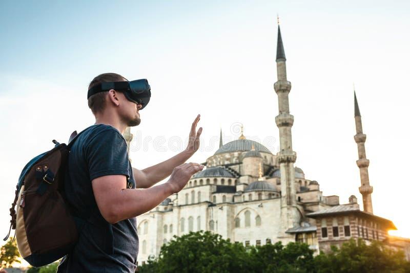 En handelsresande med virtuell verklighetexponeringsglas Begreppet av det faktiska loppet runt om världen I bakgrunden blåtten royaltyfri fotografi