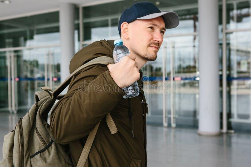 En handelsresande sätter på en ryggsäck eller lyfter den och rymmer en flaska av vatten i hans hand arkivfoton
