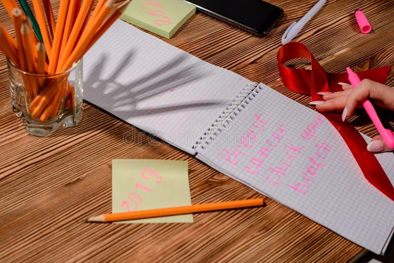 En handhåll för ung kvinna öppnade anteckningsboksidor med den rosa blyertspennan i mörk trätabell handstilen ett plan för  arkivfoton