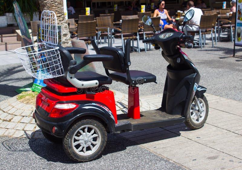 En handikappsparkcykel som hyras av en ferietillverkare i Playa Las Americas i Teneriffe i kanariefågelöarna royaltyfria foton