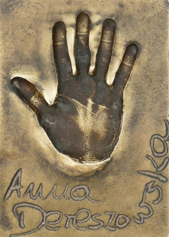 En handprint av den berömda polska aktrins och sångaren Anna Dereszowska gjorde i en mässingsplatta arkivbilder
